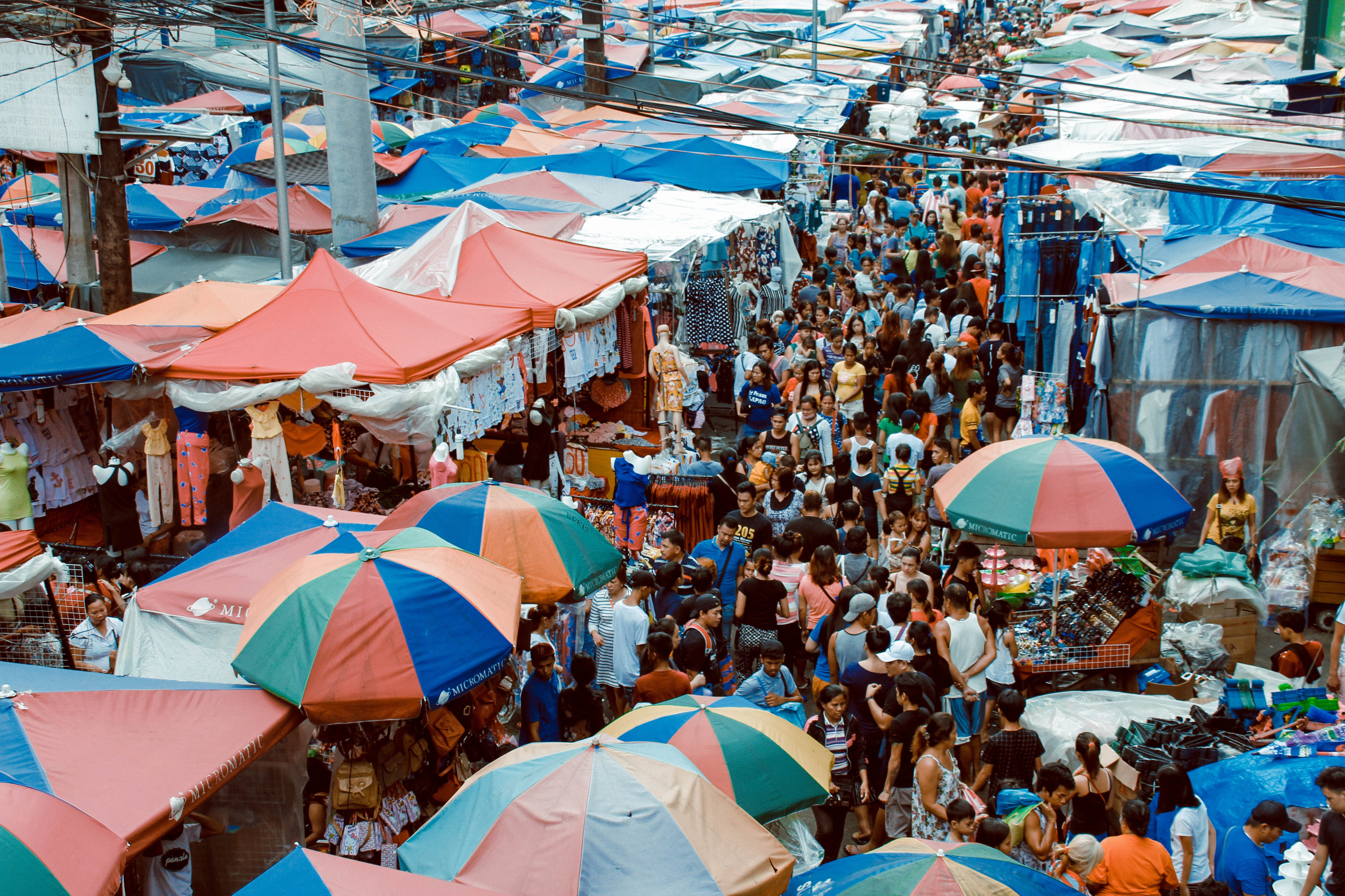 A busy inner-city market filled with fabric structures built by temporary event staff.